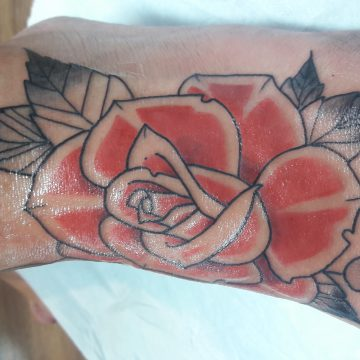 tatouage rose rouge sur le pied